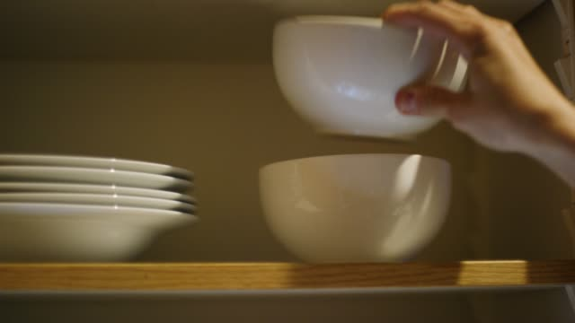 A Caucasian Woman's Hand Places Clean Bowls of Various Sizes into an Open Kitchen Cupboard Then Closes the Door