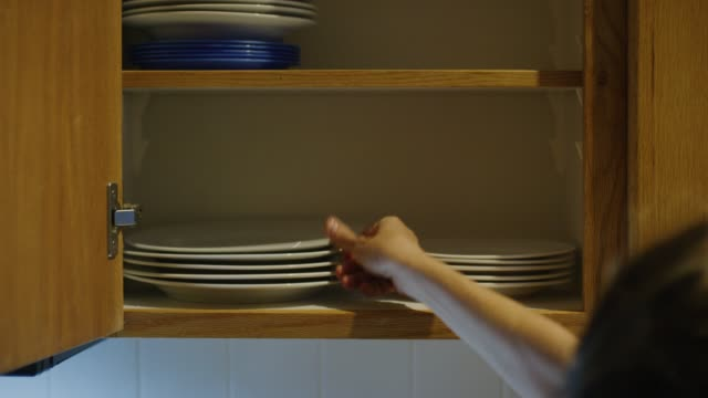 A Caucasian Woman's Hand Places Clean Plates of Various Sizes into an Open Kitchen Cupboard