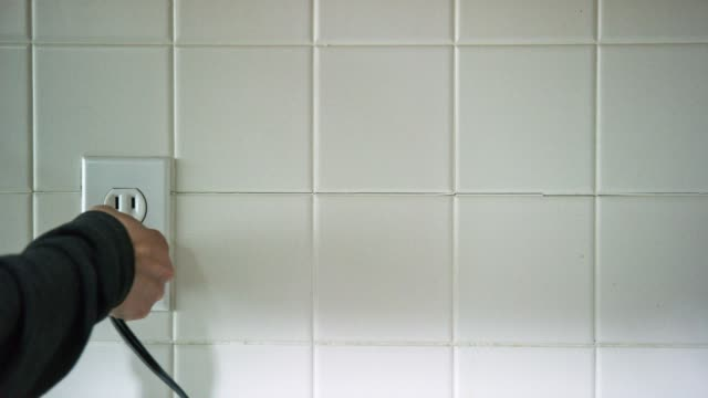 a caucasian woman's hands plug an electrical cord into a vertical american electrical outlet then unplugs the cord - collega video stock e b–roll