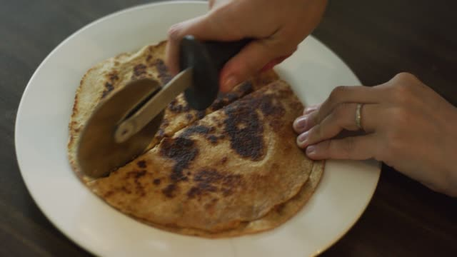 A Caucasian Woman's Hands Use a Pizza Cutter to Slice a Cooked Quesadilla (Tortilla and Cheese) into Eight Pieces on a Plate