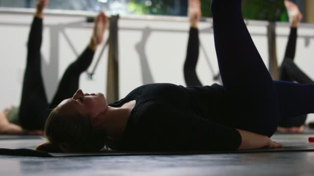 una donna caucasica sulla ventina guida la sua lezione di ginnastica nel definire le estensioni delle gambe del pilates in una palestra - metodo pilates video stock e b–roll