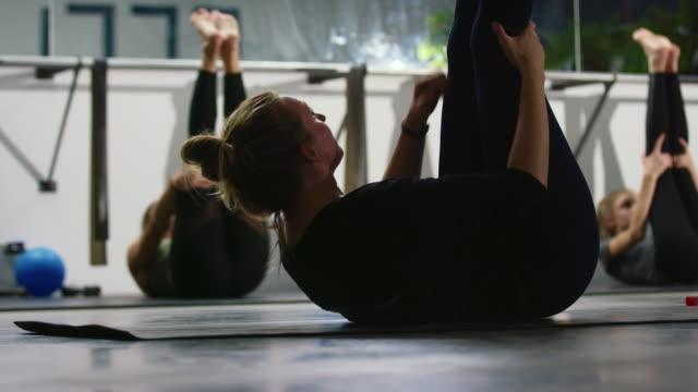 una donna caucasica sulla ventina guida la sua lezione di ginnastica in sit-up pulsante pilates con gambe estese in palestra - metodo pilates video stock e b–roll