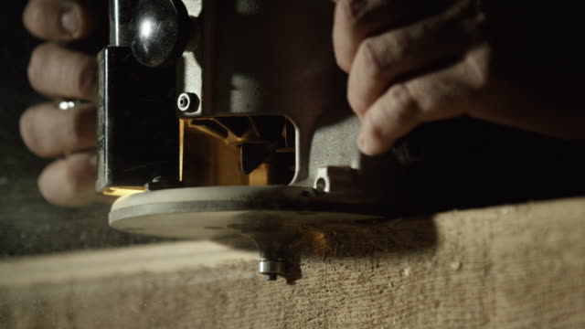 a caucasian woodworker uses a router along the edge of a red oak board as sawdust sprays into the air - trociny wytworzony przedmiot filmów i materiałów b-roll