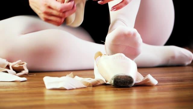vídeos de stock, filmes e b-roll de a bailarina branca em preto tutu vestido sapatos pointe em seus pés. a arte do balé. dança clássica. preparação para o treinamento. câmera lenta. close-up. - balé