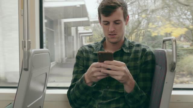 stockvideo's en b-roll-footage met kaukasische jonge mannelijke volwassen texting terwijl het berijden van de tram - bushalte