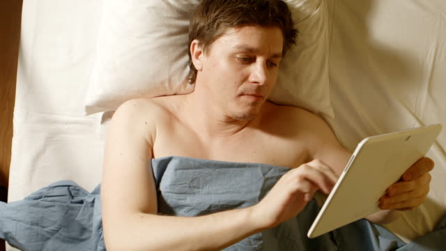Caucasian young man types a tablet PC in a bed video
