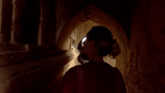 Caucasian young woman contemplating inside Bagan temple, Burma, Myanmar Caucasian young woman contemplating inside Bagan temple, Burma, Myanmar  Beautiful sunlight coming through window, shot in 4K resolution, video. People travel discovery concept Asia bagan stock videos & royalty-free footage