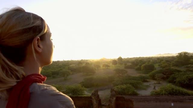 beyaz genç kadın myanmar 4 k güneş doğarken bagan arkeolojik bölge düşünürken - stupa stok videoları ve detay görüntü çekimi