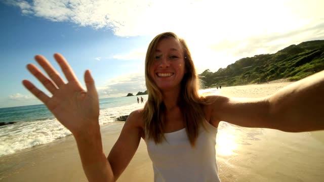 Caucasian young woman on beach takes selfie portrait video