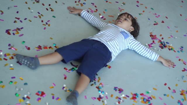 Caucasin Ethnicity little boy posing angel wings with glitter ribbon on floor