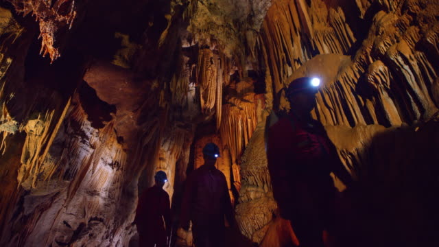 PAN Cavers walking through cave full of beautiful dripstones Wide low angle panning shot of three cavers walking through a large cave filled with dripstones on the walls and ceiling of the cave hall. cave stock videos & royalty-free footage