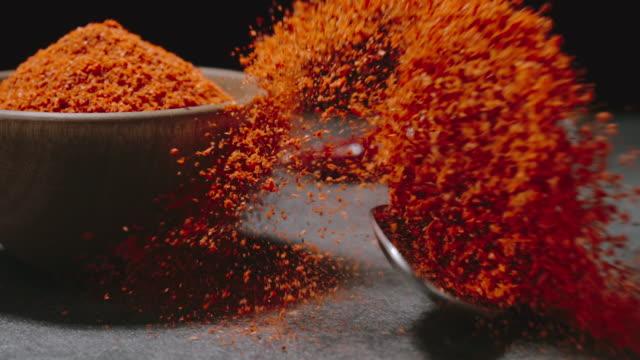 vídeos y material grabado en eventos de stock de pimienta de cayena en polvo. cuchara con chile seco cae con un chapuzón. cámara lenta - cayena guindilla roja