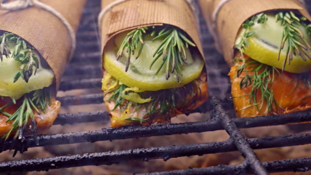 cedar plank salmon with lemon and herbs and bacon wrapped asparagus - alla griglia video stock e b–roll