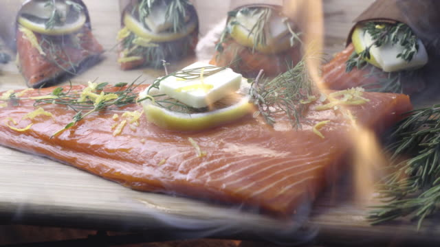 Cedar Plank Salmon with Lemon and Herbs Buttery delicious wild caught salmon in a butter lemon baste with rosemary and other fresh herbs wrapped in a thin cedar plank plank timber stock videos & royalty-free footage