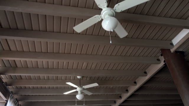 Ceiling fan rotating in an cafe with straw roof.