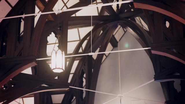 ceiling lanterns under the wooden arched roof of church architecture. - candeliere video stock e b–roll
