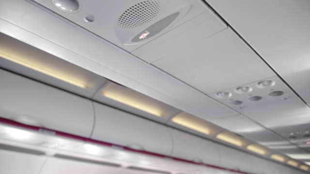 Ceiling of airplane cabin with load speaker, no smoking sign, buttons.