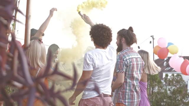 vidéos et rushes de célébration de la fête avec des bombes fumigènes colorés - man drinking terrace