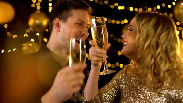 feiern sie junges paar mit dem trinken von champagner, festlichen lichtern hintergrund - champagner toasts stock-videos und b-roll-filmmaterial