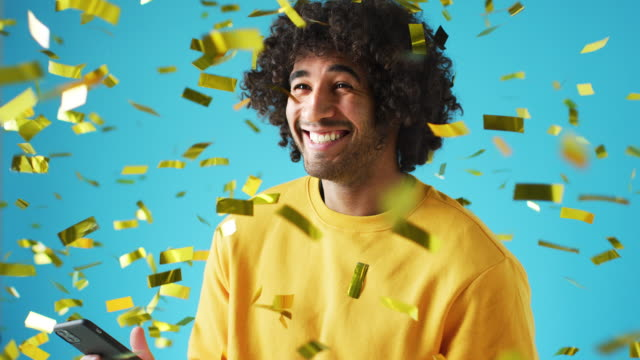 Celebrating Young Man With Mobile Phone Winning Prize And Showered With Gold Confetti In Studio video