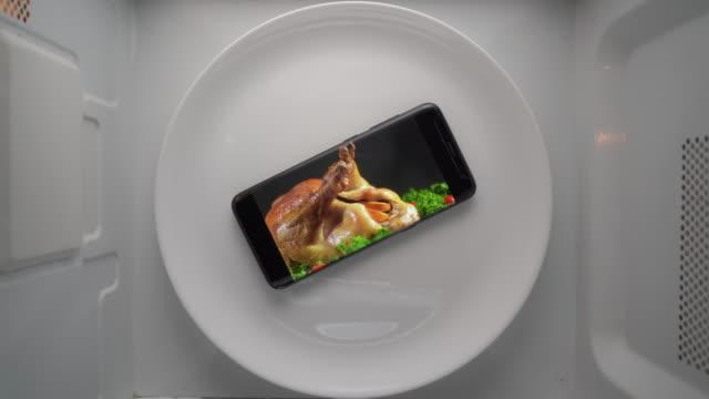 telefon komórkowy na talerzu z pieczonym indykiem dziękczynienia na ekranie w kuchence mikrofalowej. - indyk pieczony filmów i materiałów b-roll