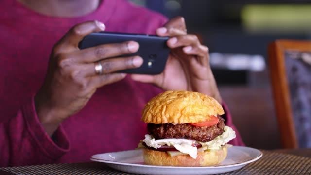 vídeos de stock e filmes b-roll de cell phone photographing a burger. hamburger on cafe table - fotografar