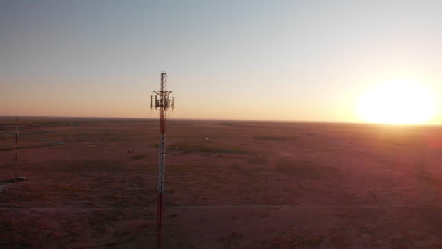 5G Cell Tower At Sunset: Cellular communications tower for mobile phone and video data transmission