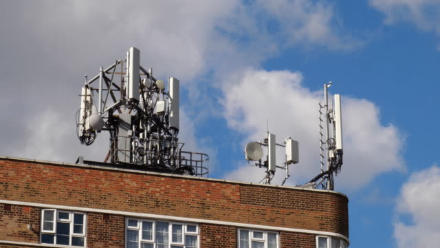 cell tower on rooftop for 5g mobile phone and communication technologies - frequenza video stock e b–roll