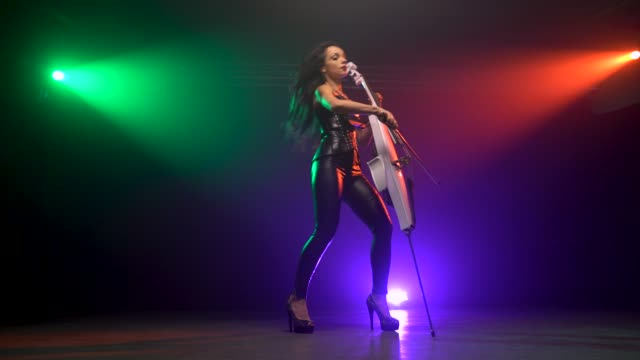 cellist with electronic cello performs on stage. - orchestra video stock e b–roll