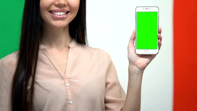Cellphone with green screen in female hand against Italian flag, translator app