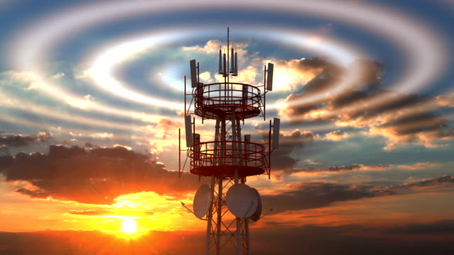 Cellular telecommunications tower with radio waves visible against sunset sky