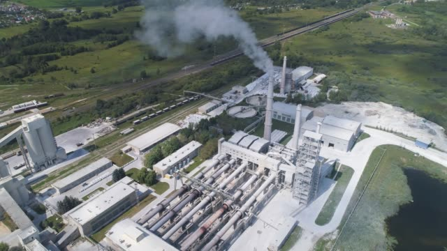 Cement factory, industrial enterprise. The smoking factory chimney. Cement factory, industrial enterprise. The smoking factory chimney. Shooting with drones, a smooth circular flight over the plant. cement stock videos & royalty-free footage