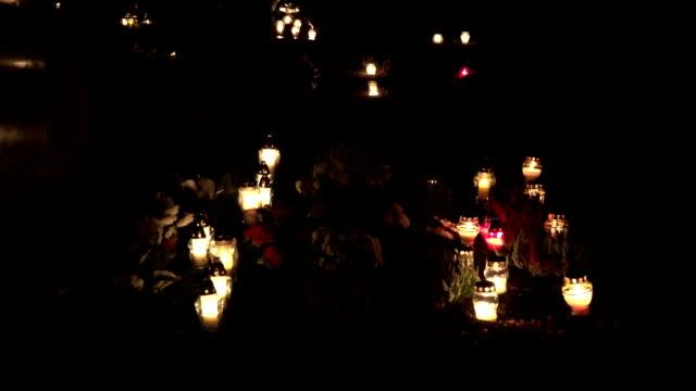 kyrkogård dekorerad med ljus för alla helgons dag på natten. oskärpa. fullhd - ljus på grav bildbanksvideor och videomaterial från bakom kulisserna