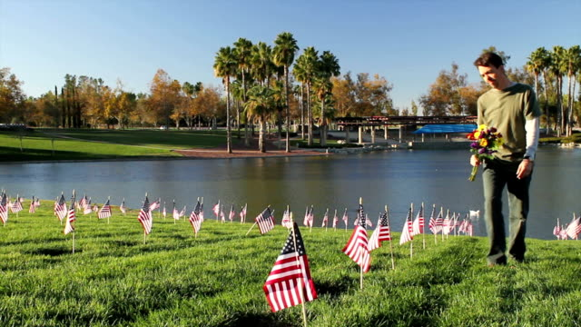 Cemetery Man Lays Flowers on Veterans Day Shot at Riverside National Cemetery in California on 11-11-12. memorial day stock videos & royalty-free footage