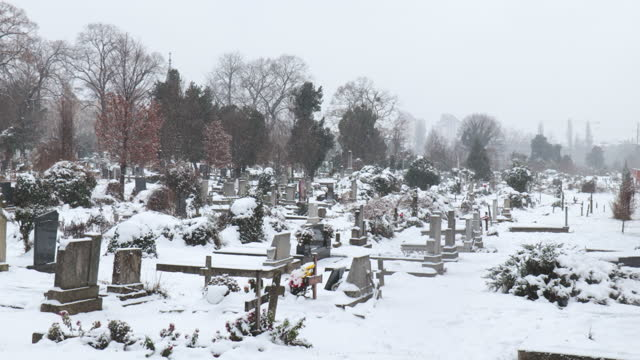 Cemetery or graveyard with graves covered with snow in the cold winter day