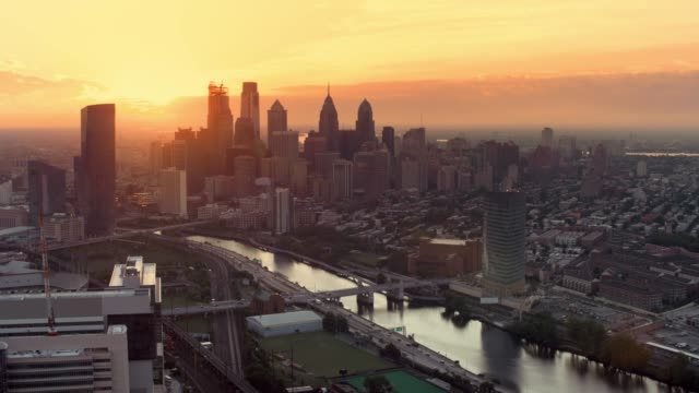 AERIAL Center City of Philadelphia, PA viewed from the Schuylkill River at sunrise Aerial shot of the Center City of Philadelphia from the Schuylkill River as the sun is rising behind the skyscrapers. Shot in PA, USA. sunrise dawn stock videos & royalty-free footage