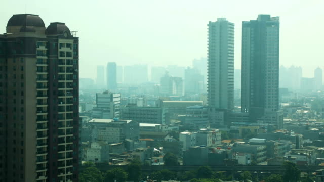 Central Jakarta elevated residential city scene on a smoggy day HD time lapse Central Jakarta elevated city scene on a overcast day HD time lapse looking towards East Jakarta, featuring tall apartment buildings and the rooftops of smaller habitations jakarta stock videos & royalty-free footage