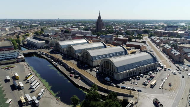 central market in riga city historical europe town living houses and building with roads and cars traffic drone flight - łotwa filmów i materiałów b-roll