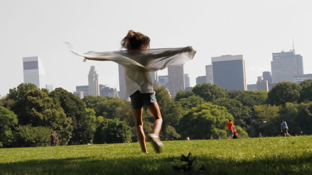 Central Park Manhattan. View from the grass with the skyscrapers at the background. A little girl play turning arround with a bandanna video