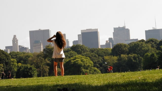 Central Park Manhattan. View from the grass with the skyscrapers at the background. A little girl enter on a picture walking on her back in slow motion video