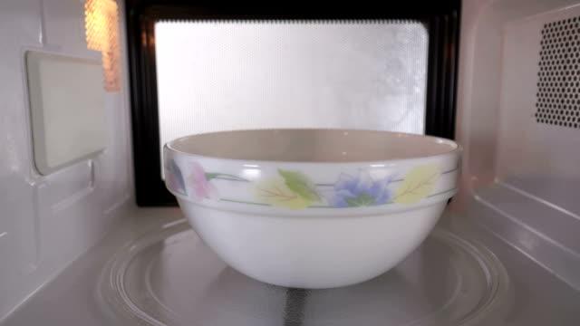 vídeos y material grabado en eventos de stock de tazón de cerámica con algo de comida se calienta en el microondas spinning en bandeja giradiscos - cuenco
