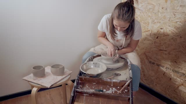 Ceramist master woman is making tableware using traditional potter's wheel Female potter is working with potter's wheel, modeling handmade clay bowls. She is doing her hobby and relaxing in small cozy workshop hobbies stock videos & royalty-free footage