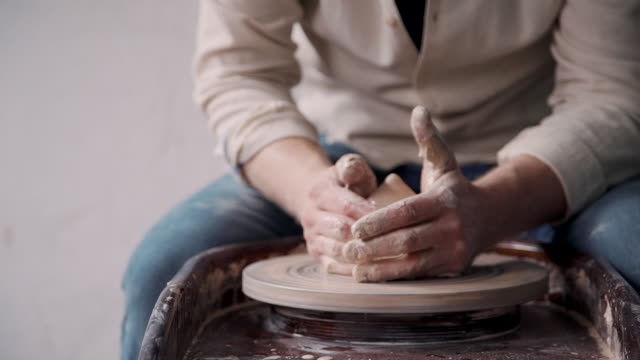 vídeos de stock e filmes b-roll de ceramist person holding clay in hands and making earthenware in - teacher school solo
