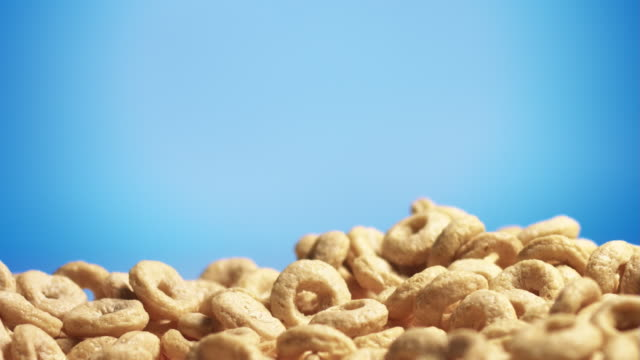Cereal rings falling on blue background video