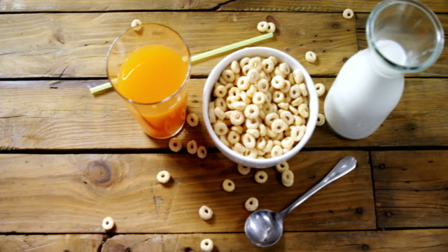 Cereal rings, orange juice and milk on wooden table 4k video