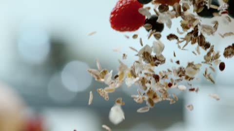 slo mo cereali cadere in una ciotola piena di yogurt - alimentazione sana video stock e b–roll