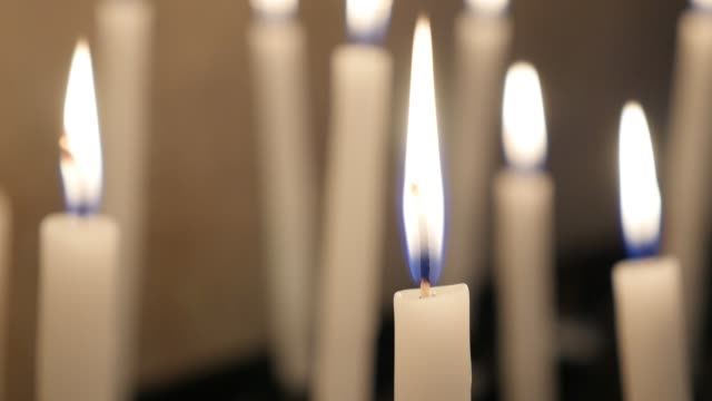 Ceremonial white votive wax candles in cathedral fired and burning
