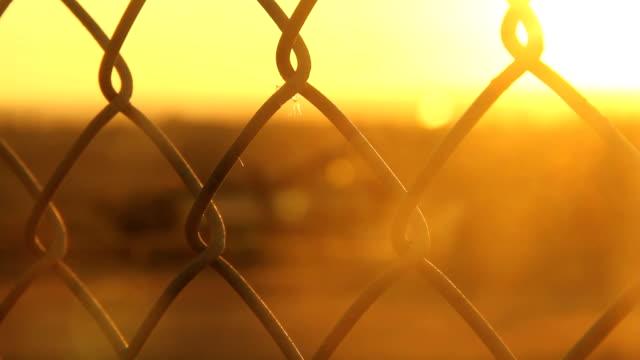 stockvideo's en b-roll-footage met chain fence against golden sun - kaderrand
