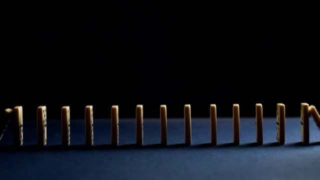 Chain reaction of dominoes toward each other. Domino Effect video