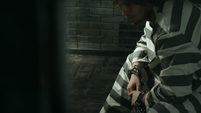 Chained men sitting in prison cell video